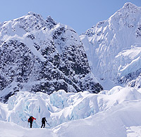 Photo by Jia Condon. Two mountain climbers carry gear to a peak.