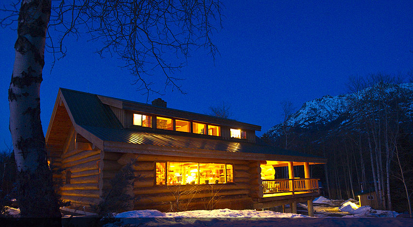 Log lodge is lit up on a winter's night.